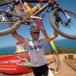 Urs Huber streckt sein Rad vor Freude über den Sieg auf dem Grassy Hill vor dem Pazifik in die Höhe (Foto: crocodile-trophy.com)